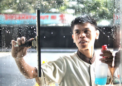 A man from Patra Supplies & Services cleaning a window